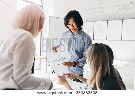 Asian Male Office Worker With Wristwatch Holding Documents With Diagrams While Talking With Female C