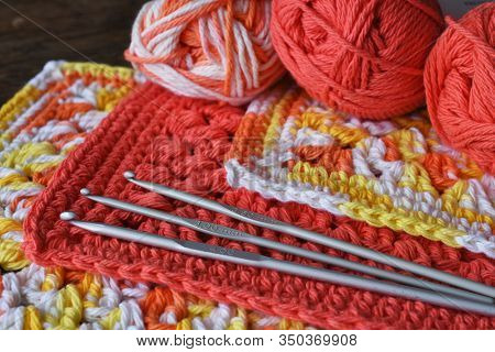 A Top View Image Of Crochet Wash Cloths And Three Metal Crochet Hooks.