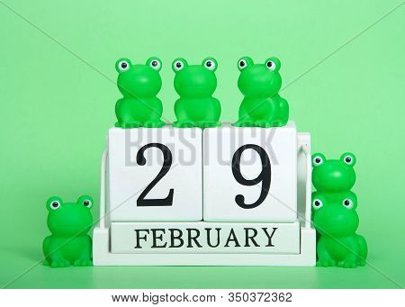 White Calendar Blocks February 29 On Green Background With Generic Green Frogs On And Around Calenda