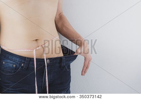 Close Up Shot Of Man With Slim Body Measuring His Waistline And Torso. Healthy Nutrition, Diet And W