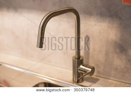 Kitchen Sink Of Dark Gray Stone With Chrome Faucet In A Clean Kitchen With A Glossy Work Surface, Cl