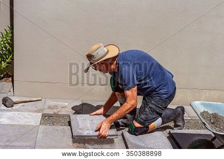 Male Retiree Laying Paving Stones In His Own Backyard As A Weekend Project