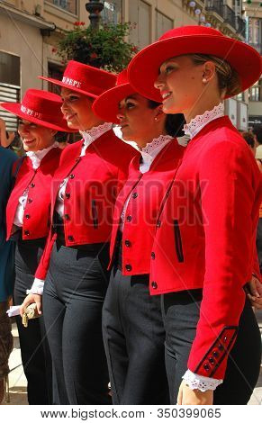 Malaga, Spain - August 18, 2008 - Row Of Women In Red Hats And Coats At The Tio Pepe Promotion Durin