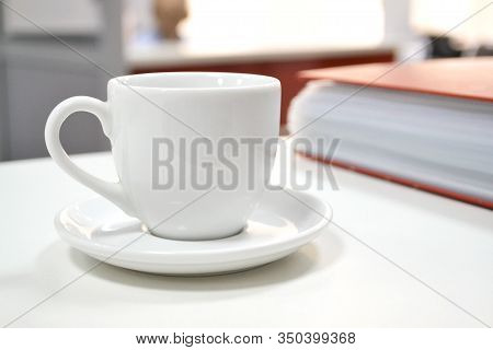 Coffee Break. White Cup For Tea Or Coffee On A White Office Desk Near A Red File Folder And Hardcove