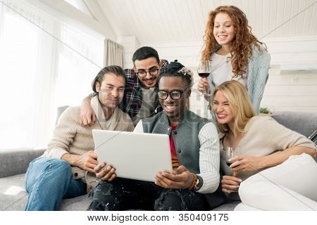 Group of cheerful multi-ethnic friends having fun looking at photos on laptop together, horizontal shot