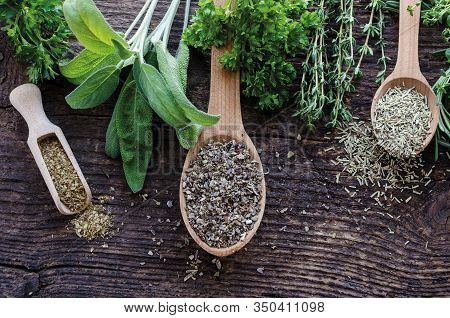 Assorted Fresh And Dry Herbs On An Old And Vintage Wooden Background. Sage, Rosemary, Thyme And Pars