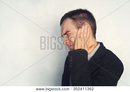 Man With Earache Is Holding His Aching Ear Body Pain Concept. A Businessman Or Working With Tinnitus