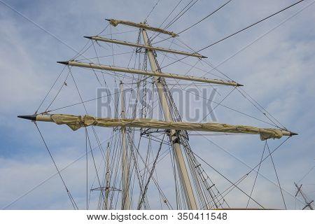 Rigging Of A Tall Ship Below A Blue Cloudy Sky In Sunlight In Winter