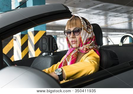 Young Woman In Sunglasses, In A Headscarf Driving Convertible Car. Blond Fashion Model Indoor Underg