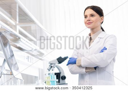Confident Caucasian female doctor wearing white lab coat and gloves standing with arms crossed in modrn laboratory