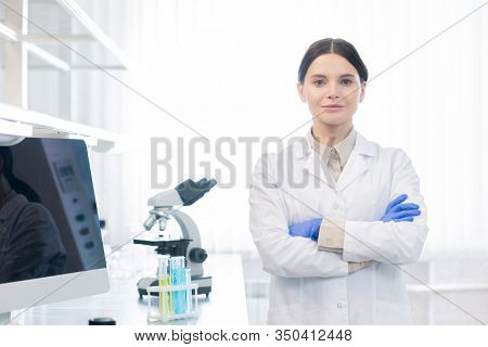 Confident Caucasian woman wearing white lab coat and gloves standing with arms crossed looking at camera