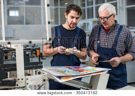 Busy printing plant workers standing at printed pages and choosing colors for next printing
