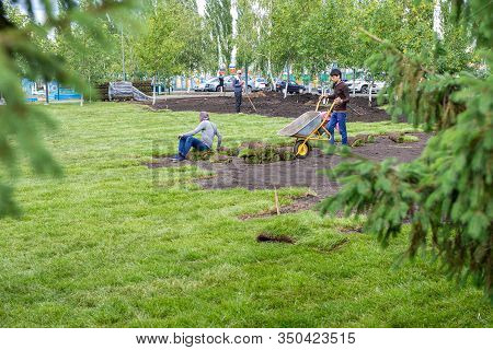 Workers Are Laying Sod Lawn Rolls. Landscaping Of Yard, Landscaping Of City Park. Yfa, Russia - 28.0