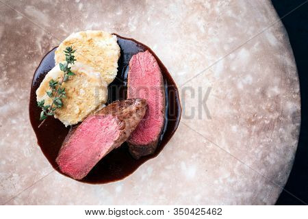 Fried dry aged venison tenderloin fillet medallion steak natural with bread dumpling and spicy gravy sauce as top view on a modern design plate with copy space