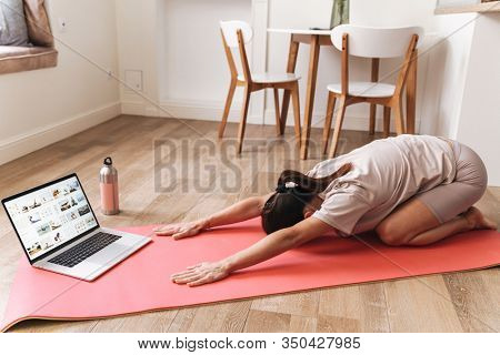 Image of a concentrated young beautiful brunette fitness woman make stretching exercises indoors at home near laptop computer.