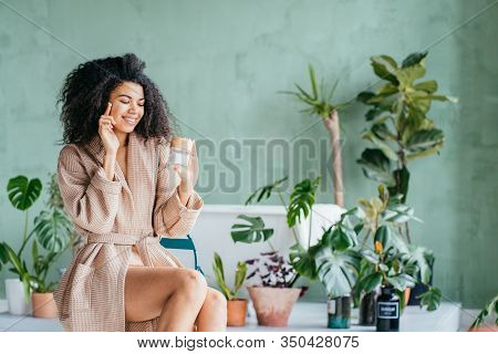 Funny Smiling Eco Friendly African Young Woman In Bathrobe Apply Cream On Face, Hold Cream Jar Point