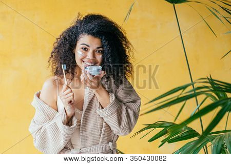 Young Friendliness African American Woman Dressing Beige Gown Holding Eco-friendly Bamboo Toothbrush