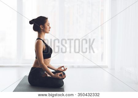 Ardha Padmasana Exercise. Side View Of Fit Girl Meditating Sitting In Lotus Pose On Gray Yoga Mat By
