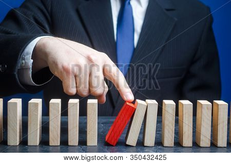 Businessman Starts The Process Of Falling Dominoes. Starting Work After Stopping. Continuation Of Wo