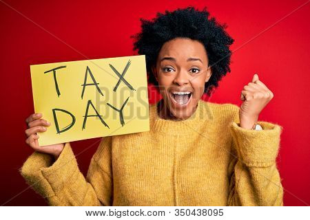 Young African American afro woman with curly hair holding paper with tax day message screaming proud and celebrating victory and success very excited, cheering emotion