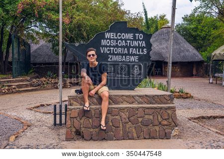 Victoria Falls, Zimbabwe - April 8, 2019 : Tourist Sits On The Welcome Sign Placed At The Entry Gate