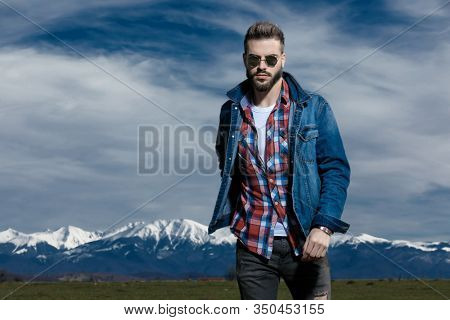 Tough man looking forward while wearing jeans jacket and sunglasses, moving on outdoor nature background