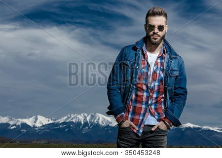 Serious man holding both hands in his pockets while wearing jeans jacket and sunglasses, standing on outdoor nature background