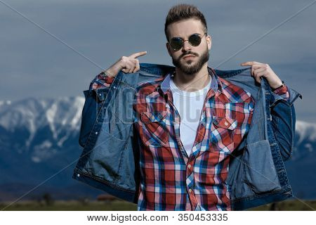 Tough man adjusting his jacket and pointing to himself while wearing jeans jacket and sunglasses, standing on outdoor nature background