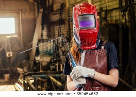 Strong And Worthy Pretty Redhead Ginher Woman Wearing Protection Helmet And Leather Apron With Glove