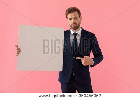 Unsure businessman holding a blank billboard and pointing to it while standing on pink studio background