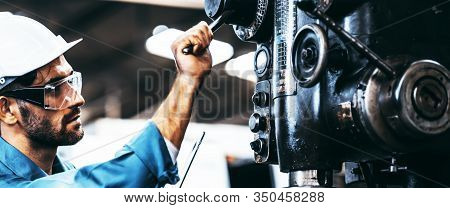Engineer Looking Of Working At Industrial Machinery Setup In Factory. Manual Workers Cooperating Whi