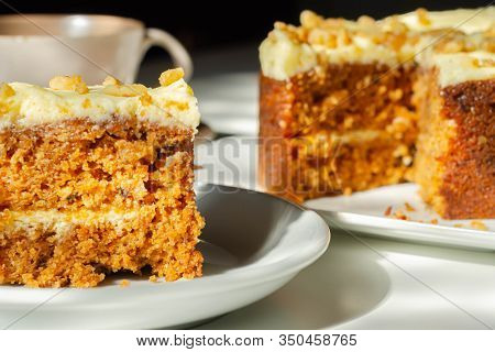 Sliced Carrot Cake Filled And Topped With Cream Cheese Buttercream And Decorated With Walnuts