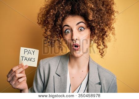 Young business woman with curly hair holding pay taxes to goverment reminder over yellow background scared in shock with a surprise face, afraid and excited with fear expression