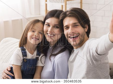 Capturing Happy Moments. Self-portrait Of Millennial Parents With Cute Little Daughter Posing For Se