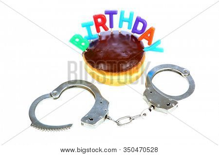 Birthday Donut. Cream Filled Chocolate Donut with Handcuffs. Isolated on white. Room for text. Birthday Donut and Handcuffs for someone special. Police Handcuffs with Donuts for a special party.
