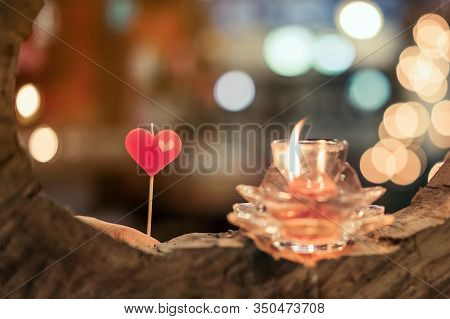 A Red Heart Shaped Candle And Candlelight In Small Glass Cup To Decorate On Valentine's Day With Bok
