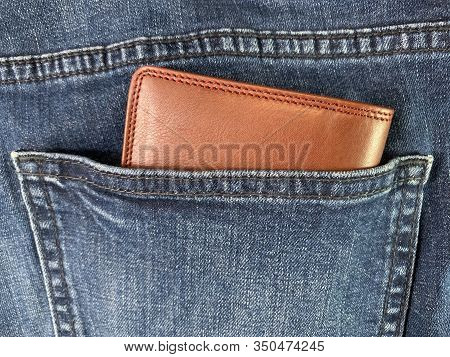 Men's Wallet In The Back Pocket Of Jeans. Leather Brown Wallet In Blue Jeans.