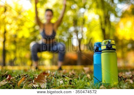 Two Bottles Of Water On Green Grass. Sporty Woman Doing Outdoor Workout In Park On Background. Focus