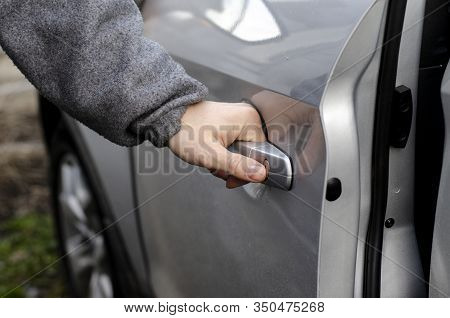 The Mans Hand Opens The Door Of The Silver-colored Car
