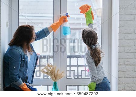 Mother And Daughter Child In Rubber Gloves With Detergent And Rag Washing Windows Together. Girl Hel