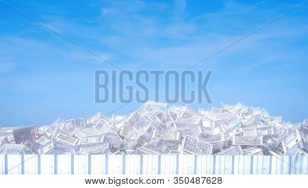 Pile Of White Plastic Basket At Factory Outdoor Warehouse. Many Of Empty Plastic Basket Against Blue