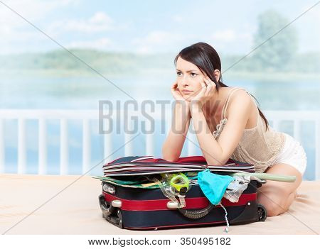 Preparations For The Voyage. A Young Sexy Woman Tries To Put Her Things In A Suitcase At Home, Sitti