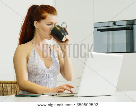 Beautiful Young Woman With Red Hair Sitting With A Laptop And Drinking Coffee.