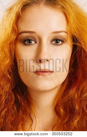 Portrait Of A Beautiful Woman With Curly Red Hair And Green Eyes.