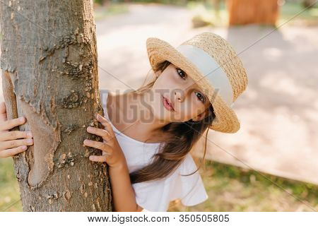 Cute Female Child With Big Black Eyes Posing Beside Old Tree During Walk In Park. Outdoor Portrait O