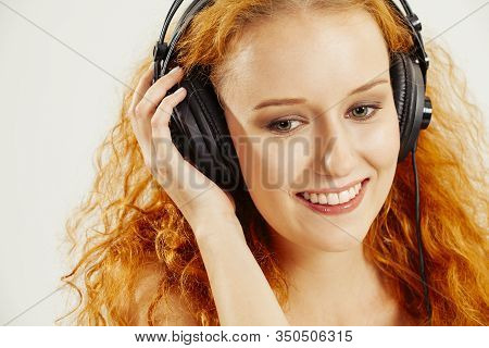 Photo Of A Beautiful Young Redhead Listening To Headphones And Smiling.