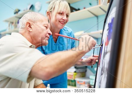 Senior man and therapist are painting together in creative painting therapy