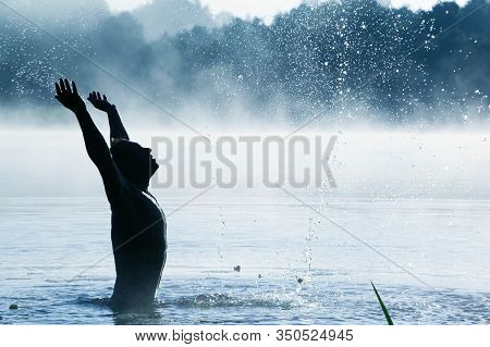 A Man On A Belt In The Water, Splashing Water In The Sides. With Fog.
