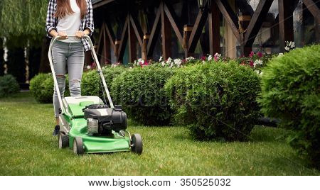 Horizontal Crop Of Woman In Casual Outfit Using Lawn Mower On Backyard. Selective Focus Of Young Gar