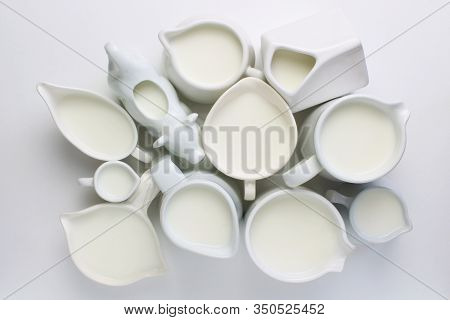 Above View Of A Large Group Of Ceramic Creamers Filled With Milk.